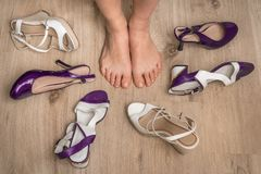 Woman choosing shoes and many shoes on wooden floor stock image