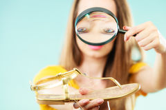 Woman choosing shoes searching through magnifying glass Royalty Free Stock Photos