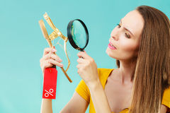 Woman choosing shoes searching through magnifying glass Royalty Free Stock Photo