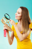 Woman choosing shoes searching through magnifying glass Royalty Free Stock Images