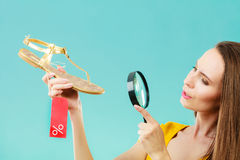 Woman choosing shoes searching through magnifying glass Stock Images