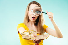 Woman choosing shoes searching through magnifying glass Royalty Free Stock Photography