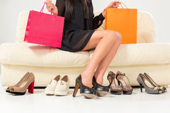 Woman choosing shoes or trouble with high heels. Shopping. Stock Photo