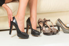 Woman choosing shoes or trouble with high heels. Shopping. Stock Photos