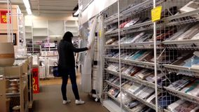 Woman choosing shower curtain inside home outfitters store stock footage