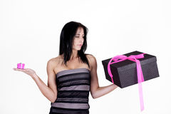 Woman choosing between small and large gifts. Sexy woman choosing between small and large gifts Stock Photos