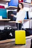 Woman choosing suitcase in shop. Young happy woman choosing travel suitcase in haberdashery store Royalty Free Stock Image