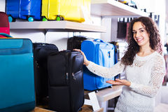 Woman choosing suitcase in shop Stock Photo