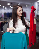Woman choosing sweater at clothing store Stock Images