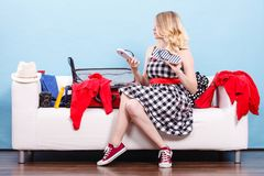Woman choosing things to pack into suitcase stock photo