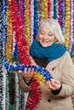 Woman Choosing Tinsels At Christmas Store Stock Image
