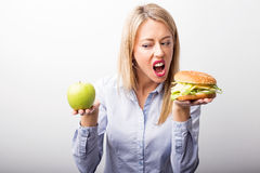 Woman choosing to eat burger instead of apple Stock Images