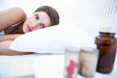 Woman choosing to take pills or not. At home in the bedroom Royalty Free Stock Images