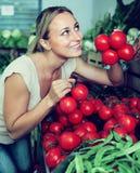 Woman choosing tomatoes on market Royalty Free Stock Photo