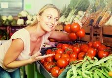 Woman choosing tomatoes on market Stock Photos