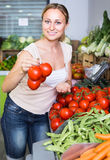 Woman choosing tomatoes on market Royalty Free Stock Images