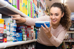 Woman choosing toothpaste in supermarket Royalty Free Stock Photos