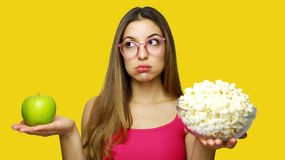 Woman choosing between unhealthy bowl of pop corn and an healthy green apple looking to the side. Girl comparing food options. Having a hard time choosing on royalty free stock photography