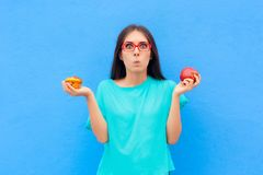 Woman Choosing Between Unhealthy Muffin and Healthy Apple. Girl comparing dessert options having a hard time choosing the best food Royalty Free Stock Photo