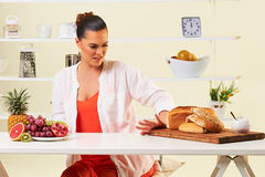 Woman choosing various fruit eating healthy diet over carbohydrates and breads. Royalty Free Stock Image