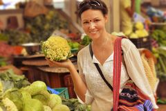 Woman choosing vegetables on market. Beautiful young woman choosing vegetables on market Royalty Free Stock Images