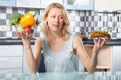 Woman choosing between vegetables and sandwich Stock Image