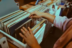 Woman is choosing a vinyl record. In a musical store stock photos