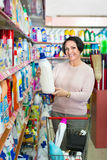 Woman choosing washing detergent in household department Stock Image
