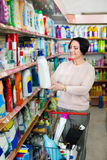 Woman choosing washing detergent in household department Royalty Free Stock Photography