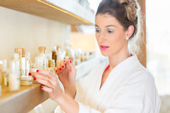 Woman choosing wellness spa products. Woman in bath robe choosing face care products in wellness spa stock photos