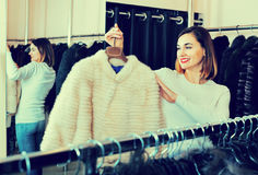 Woman choosing white mink jacket in women's cloths store. Cheerful positive smiling woman choosing white mink jacket in women's cloths store Royalty Free Stock Photos