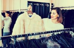 Woman choosing white mink jacket in women's cloths store Stock Photo