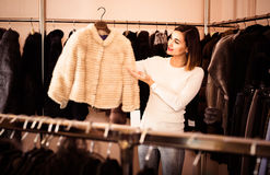 Woman choosing white mink jacket in women's cloths store Royalty Free Stock Photography