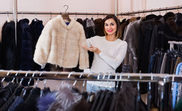 Woman choosing white mink jacket in women's cloths store. Young happy cheerful positive woman choosing white mink jacket in women's cloths store Stock Photography