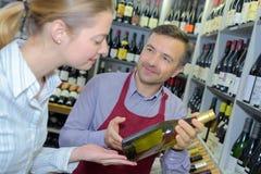 Woman choosing wine being helped. Wine stock photo