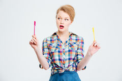 Woman choosing between yellow and red pen. Young woman choosing between yellow and red pen isolated on a white background Stock Images