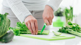 Woman chopping celery Royalty Free Stock Images