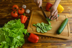 Woman chopping cucumber for salad, healthy food concept Royalty Free Stock Photo