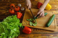 Woman chopping cucumber on wooden board, top view Royalty Free Stock Photography