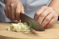 Woman chopping the garlic with knife. Royalty Free Stock Photography