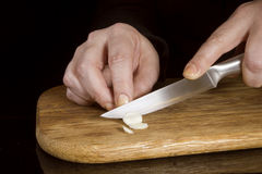 Woman chopping garlic with a knife Royalty Free Stock Photos