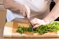 Woman chopping parsley in kitchen Stock Photos