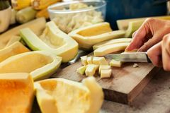 Woman chopping pumpkin slices on cutting board Stock Photo