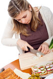 Woman chopping spring onion and preparing sandwich Stock Image