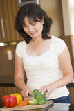 Woman Chopping Vegetables. In Kitchen Stock Images