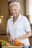 Woman Chopping Vegetables. In Kitchen Smiling Royalty Free Stock Images
