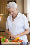 Woman Chopping Vegetables. In Kitchen Smiling Royalty Free Stock Photo