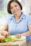 Woman Chopping Vegetables. Smiling At Camera Royalty Free Stock Images