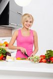 Woman chopping vegetables cooking. At home modern kitchen, young blond girl slicing prepare vegetable salad, smile Stock Image