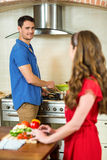 Woman chopping vegetables and man cooking on stove Royalty Free Stock Photography